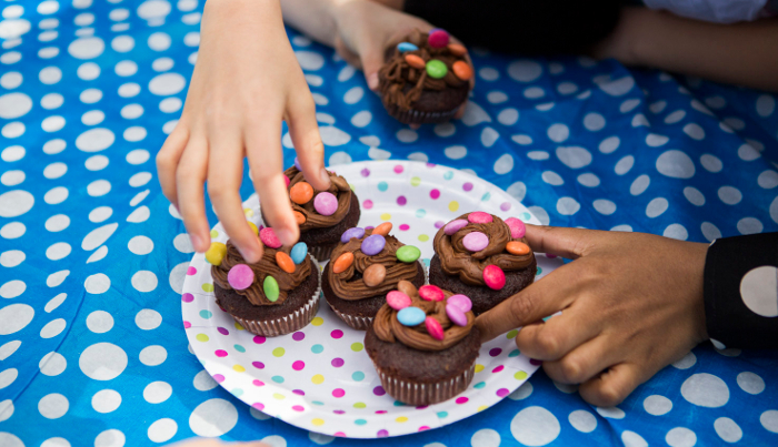 Children grab dotty cupcakes off a plate from a Dots raise lots event