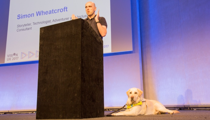 Photo of Simon and his guide dog on stage at the conference