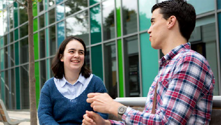 Two young people talk outside an office.