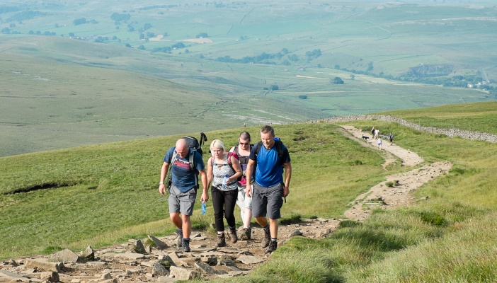 Image shows 4 people walking uphill with their backpacks in a green mountainous area