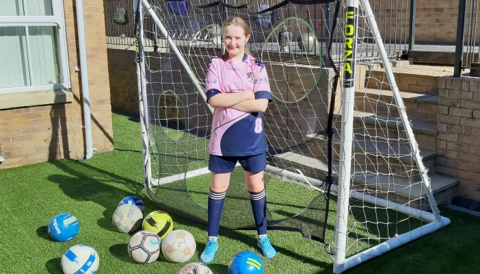 Tabitha Ryan standing in front of a goal with footballs at her feet.