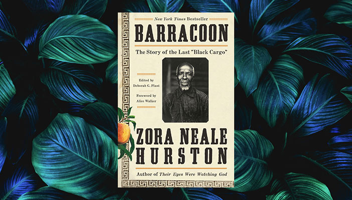 Book cover of Barracoon against a backdrop of leaves