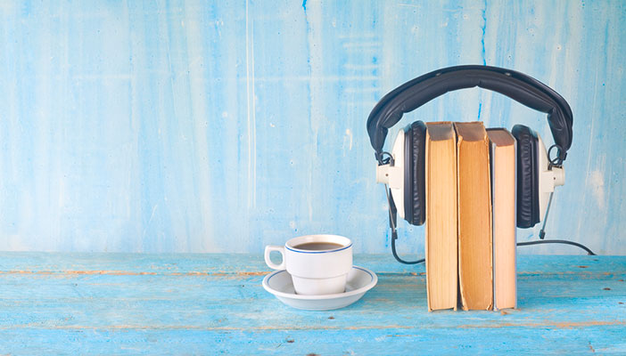 Books with headphones over them against a blue background