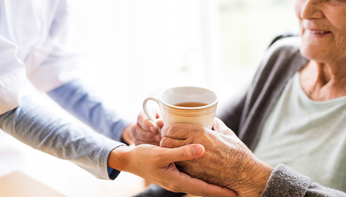 A carer's hands passing an elderly lady a cup of tea