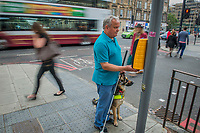 A man is standing with his guide dog waiting to cross at a controlled crossing and he is reaching for the tactile cone to tell him when it is safe to cross