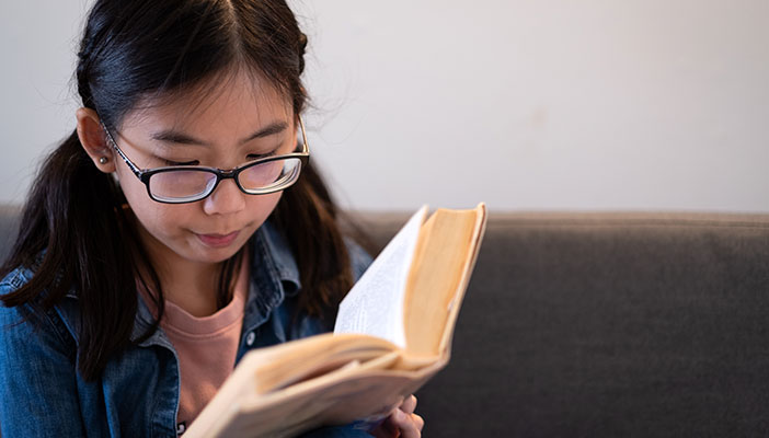 A child with glasses reading a book