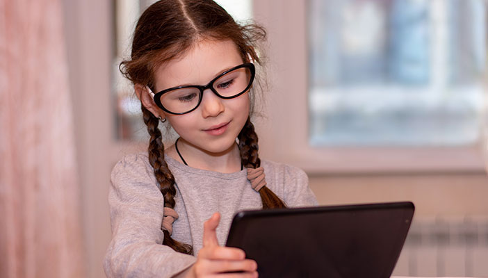 A glass wearing glasses reading using a tablet