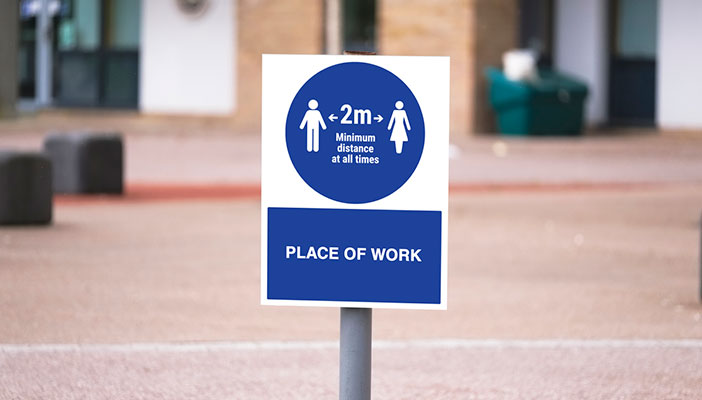 """Sign saying """"Place of work"""" with social distancing reminder"""