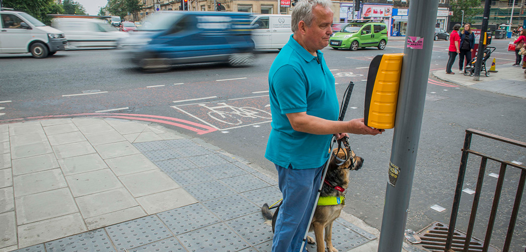 Alan feels for the tactile cone at a crossing in Edinburgh