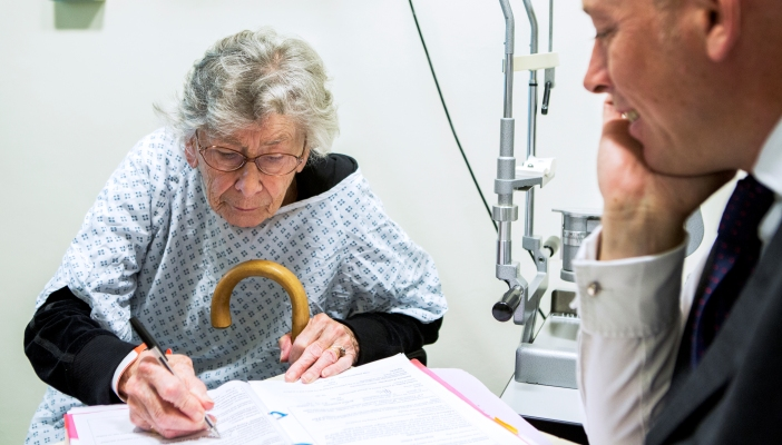 Lady sitting up in a hospital bed and filling in a form