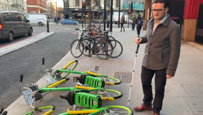 Image of RNIB Policy and Campaign Manager Hugh Huddy standing on a pavement, next to three dockless bikes lying on their sides.
