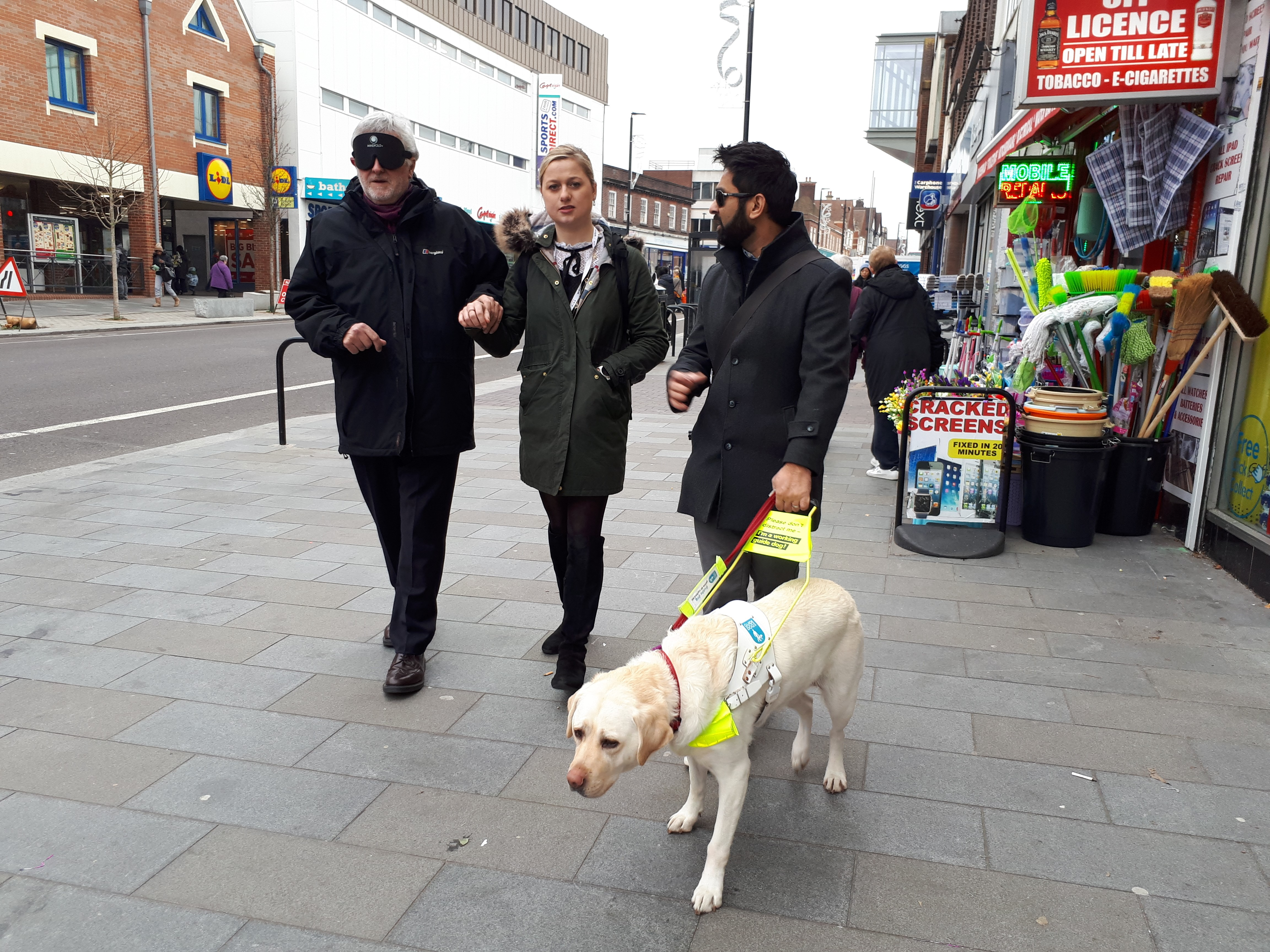 Image shows MP Clive Efford blindfolded and being guided down a street by Emily Marr, RNIB's Parliamentary Affairs Officer, and next to Emily, Dr Amit Patel with his guide dog kika.