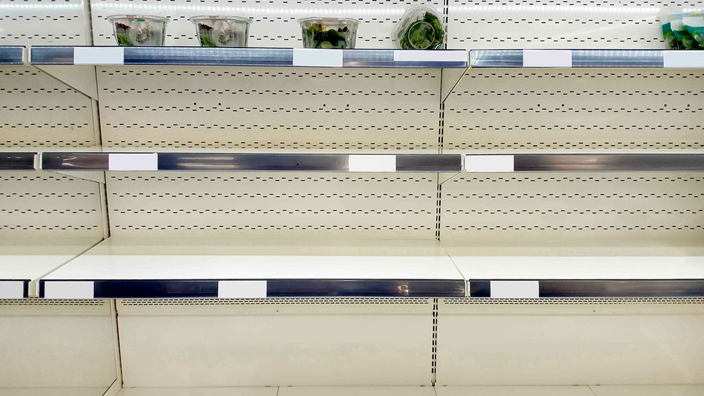 Mostly empty supermarket shelves with just a few fresh products left