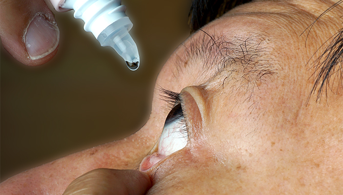 Man putting in eye drops