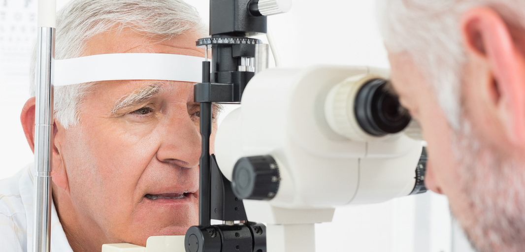 Male patient has his eyes checked by an optometrist