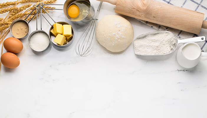 Image shows several different baking tools such as bread, butter and a whisk