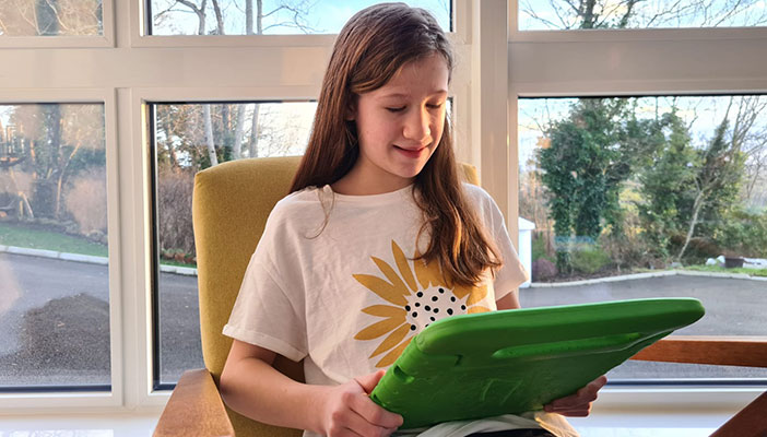 A girl at home reading using a tablet