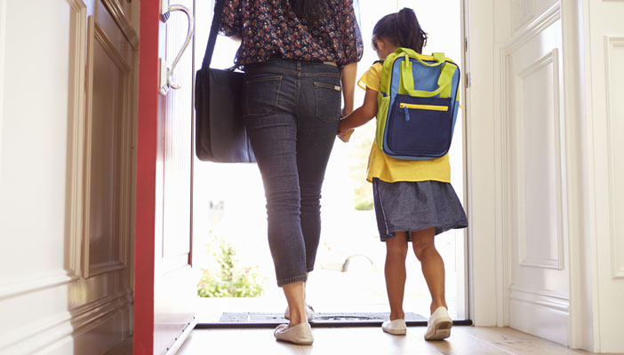 Girl holding hands with mother leaving the house