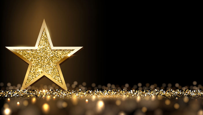 A gold sparkly star against a black background