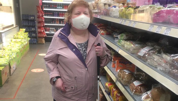 A woman with a white cane, wearing a face mask, in a grocery store
