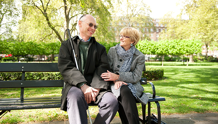 A blind man with a woman holding his arm on a bench