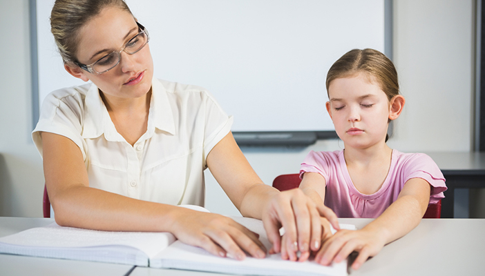 Photo of an adult and a child reading braille together
