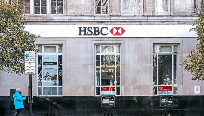 HSBC bank branch with ATMs and person walking past