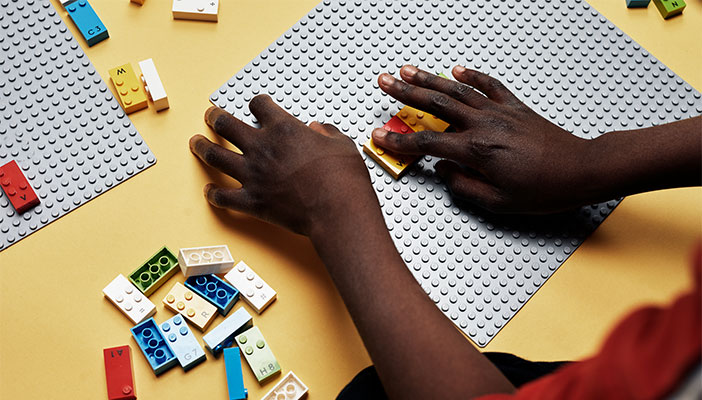 Child's hands playing with Lego braille bricks