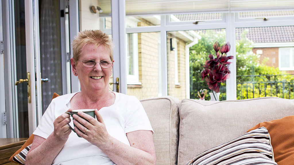 Smiling woman at home sitting on sofa in conservatory holding cup of tea