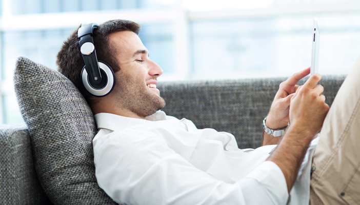 Man listening to headphone on sofa with headphones on and looking at tablet