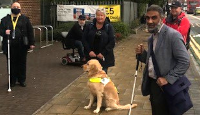 Image shows RNIB regional campaigns officer Maqsood, standing on a pavement besides Vivienne Wilkes and members of the local authority.