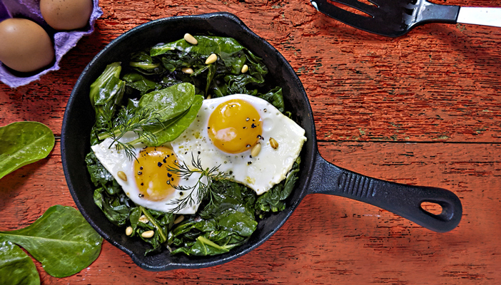 image shows a healthy looking pan of breakfast eggs and spinach cooking