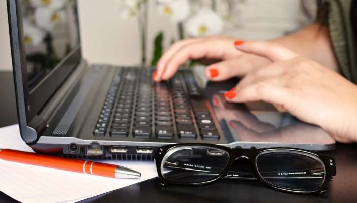 Woman typing on a laptop with glasses next to her on the desk