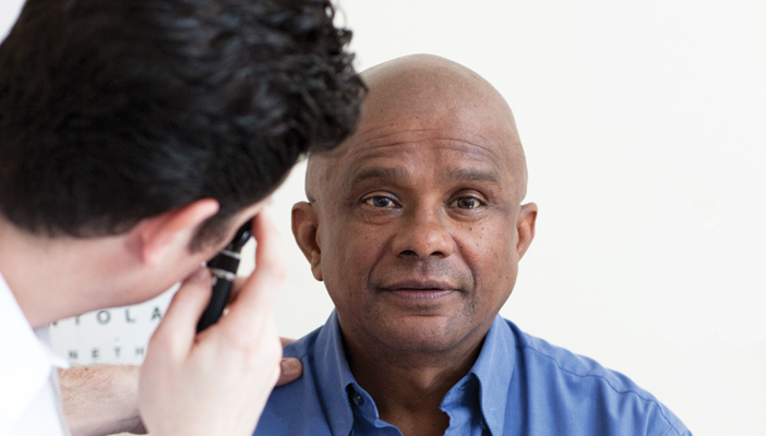 Black man having his eye examined by an optometrist with a sight test chart in the background