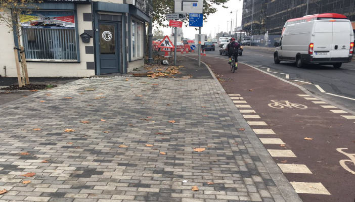 Image of a street where the kerb dividing the pavement from the cycle lane and road has been removed
