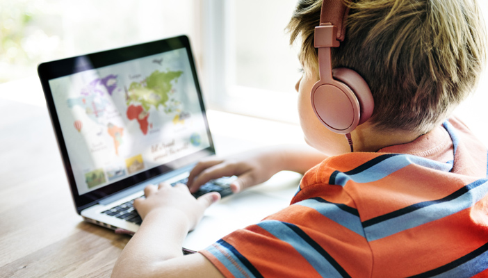Image shows a boy wearing headphones playing an audio game