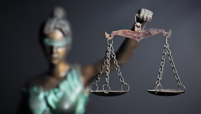 Photo of the Lady of Justice with a blindfold on and holding scales