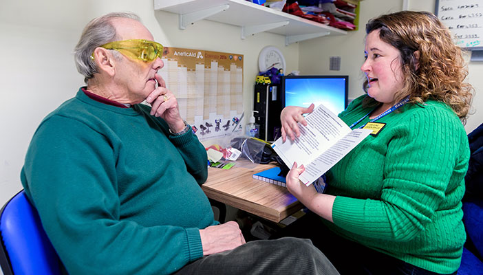 A sight loss adviser (also known as ECLO) talks with an eye health patient in her office