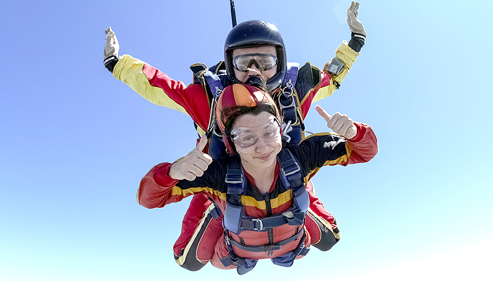 Image shows a woman harnessed to her instructor, in the air. The woman has her thumbs up and her instructor has his arms out.