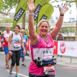 Jo smiles widely as she runs past an RNIB cheer point in the London Marathon