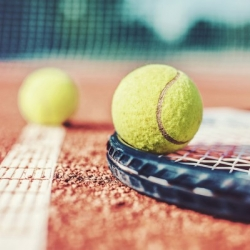 A tennis racket on a clay court with two tennis balls