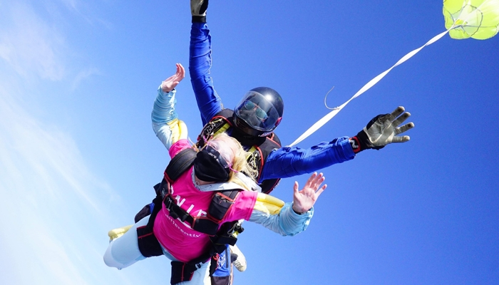 Woman freefalling mid skydive with instructor attached, both wearing face masks