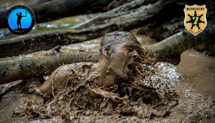 Image shows an individual mid-obstacle, coming up from the floor, with his entire face covered in mud.