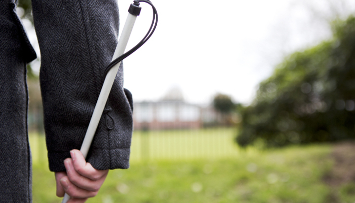 A close up of a person from behind, holding a white cane in a street
