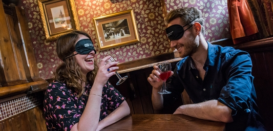 Image shows two people speed dating, drinking wine and wearing blindfolds