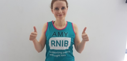 Amy wearing an RNIB vest and posing with her thumbs up