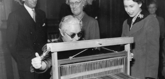 Woman sat weaving at a loom whilst Queen Elizabeth II watches