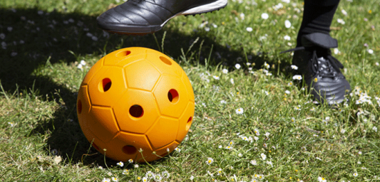 Person wearing football boots kicking yellow audible ball