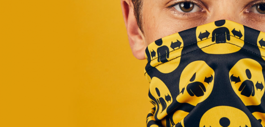 A man wearing a Please Give Me Space snood on a yellow background.