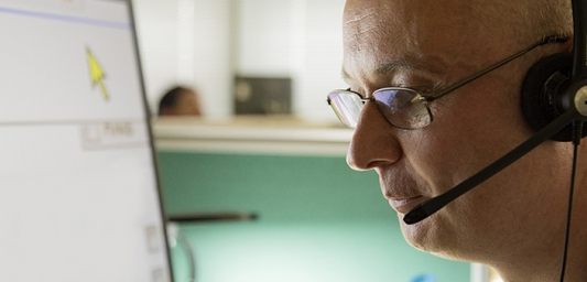 Helpline adviser with a headset in front of computer screen